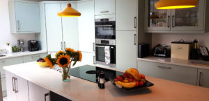 Mint kitchen units with yellow lampshades and flowers